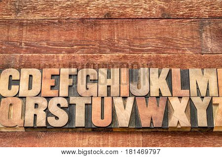 alphabet abstract in vintage letterpress printing blocks against rustic red painted barn wood with a copy space
