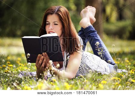 Beautiful young brunette woman lying on the meadow with field flowers with a book in her hands. Romantic outdoor conception.