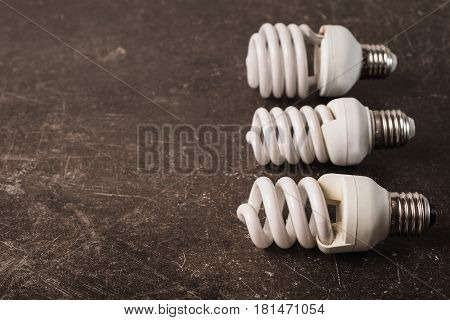 Fluorescent light bulb on a dark marble background. To save energy. Eco light bulb concept. White light bulb. Three on dark table