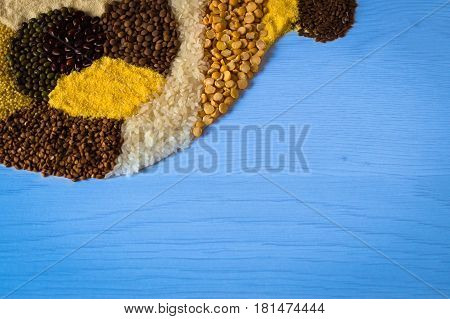 Placer of grains and cereals. Buckwheat grain, rice, pea, semolina and lentil on a blue wooden background.