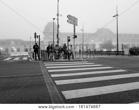 Toulouse, France - October 27, 2016; Old fashioned looking black and white smartphone image Toulouse street scene people waiting for signal to cross on pedestrian crossing in low light of cool misty morning.