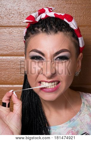 Fashion Large Portrait Of A Stylish Girl With Dreadlocks, Chewing Gum, And Stretches Her Holding Her