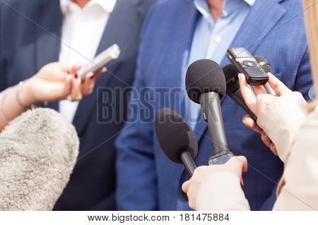 Media interview. Press conference. Broadcast journalism. Microphones.