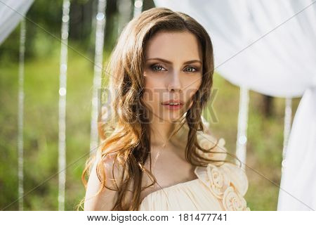 Beauty portrait of a very pretty young girl. Doll appearance. Woman with brown hair in a pink wedding dress on nature near the wedding arch. Long hair. Natural light.
