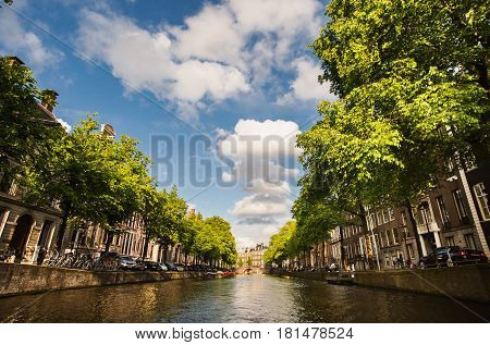 Spring sunny Amsterdam. The bright clear blue sunny sky with white clouds. Boat trip on the canals of  sunny Amsterdam. The bridge over the water. Travel to Europe. Sunny weather. Sunny city. Sunny Street