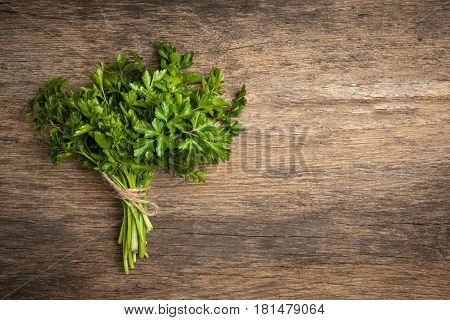 Bunch of parsley with spase for text on rustic wooden table