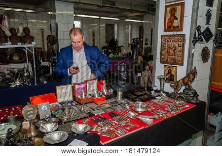 Moscow, Russia - March 19, 2017: Seller of silverware and antiques in the flea market, waiting for buyers