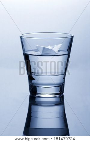 Glass of water with paper origami boat