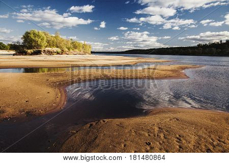 Beautiful summer landscape. Landscape with the bright clear blue sky with white clouds. Landscape with yellow sand on the beach. Water surface. The river on the plain. Green foliage. Wild nature landscape. Summer landscape. Sunny landscape. Landscape with
