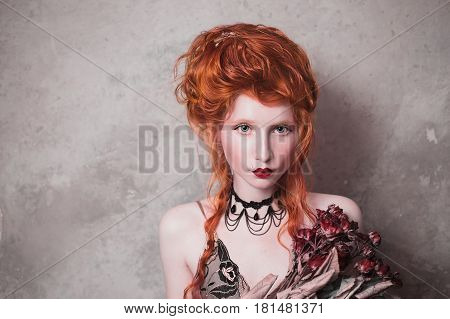 A woman with red hair in a nightgown. Red-haired woman with pale skin and blue eyes with bright unusual appearance with choker around her neck with a bouquet of dried roses. French woman courtesan. Copyspace with woman. Woman with red hair. Woman with flo