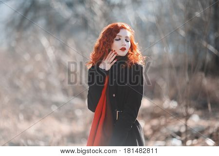 A redhaired woman with red curly hair in a black coat at the autumn background. Redhaired girl with pale skin and blue eyes and a bright unusual appearance with a scarf around her neck. Street style. Redhaired model
