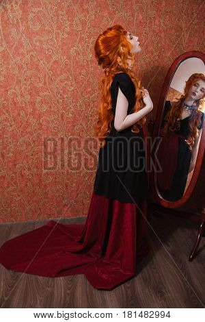 Woman with long red curly hair in a black and red dress and choker on her neck. Red-haired girl with pale skin blue eyes a bright unusual appearance and red lips on a background of a mirror