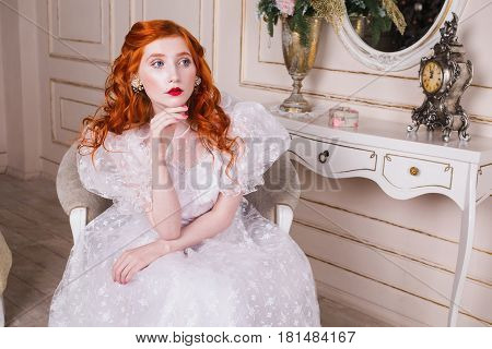 Woman  princess with long red curly hair in a white vintage wedding dress with white pearl earrings on her ears. Red-haired  princess girl with pale skin blue eyes a bright unusual appearance in the luxurious bedroom. Nice  princess. Princess in wedding d