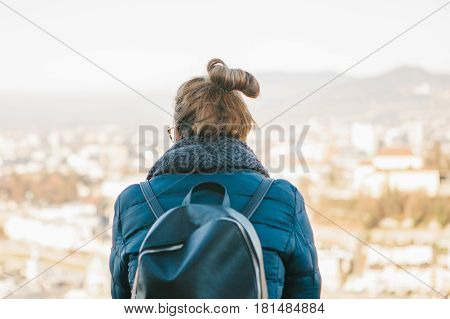 Young woman tourist on the viewpoint, admiring the view of the mountains