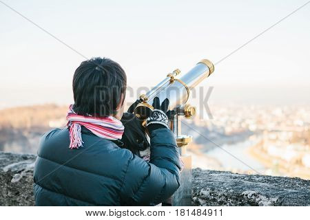 A young man with a child looks through the viewing binoculars on the observation deck on the hill in the Austrian city of Salzburg - hometown of Mozart.