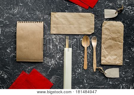 food delivery service workdesk with paper bags and flatware on gray background top view mock-up