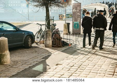 Austria, Salzburg, January 01, 2017: A poor old woman (beggar) asks for some money to live in the city of Salzburg in Austria. Poverty, unemployment.