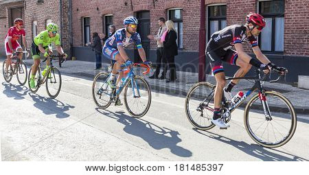 Louvil France - April 102016: Group of cyclists including Robin Stenuit of Wanty-Groupe Gobert Team riding in front of Louvil Town Hall in France during Paris Roubaix on 10 April 2016.