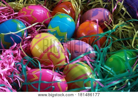 Plastic Easter Eggs provide a colorful contrast with the artificial grass in a basket