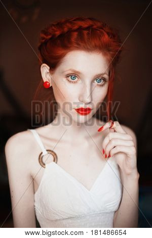 A woman with red curly hair braided in a braid in a white dress. Red-haired girl with red earrings in ear pale skin blue eyes bright unusual appearance red lips. Pin-up girl makeup. Dutch braid
