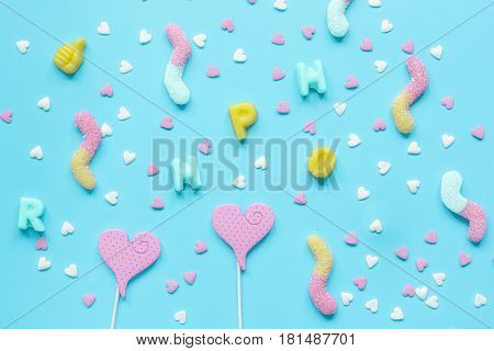 Colorful heartshaped candies scattered on blue texture background top view pattern