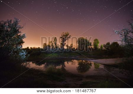 Beautiful night starry landscape. Stars reflected in the water at night. Astrophotography. Clear night starry sky. Slow shutter speed. The spectacular sky. Scenic view. Night photo with star sky