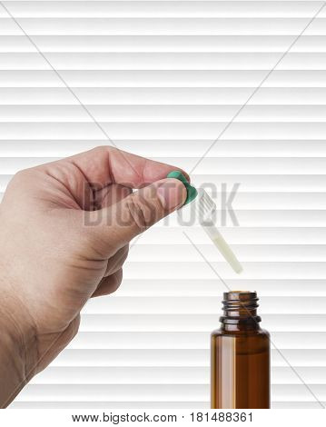 Hand man scientist, doctor keeps the pipette for drop over the container with liquid, medication or chemical substance laboratory. Isolated on white of stripes background with clipping path