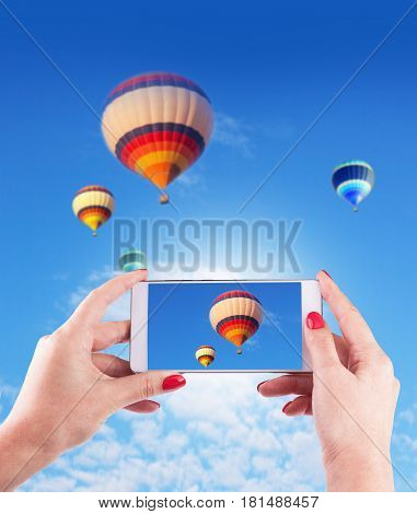 Female Hands Holding Smart Phone Displaying Photo of Blue Sky with Hot Air Balloons Behind.