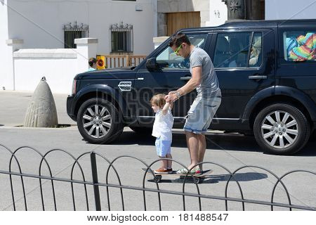 SITGES SPAIN - MAY 23: The father learns his son riding on skateboard on May 23 2015 in Sitges Spain. Up to 60 mln tourists is expected to visit Spain in year 2015.