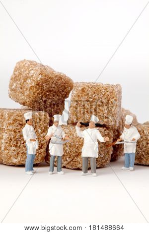 Miniature people: Chefs cook in front, cubes of brown sugar.
