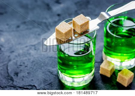 green absinthe in glass with sugar cubes on dark table background