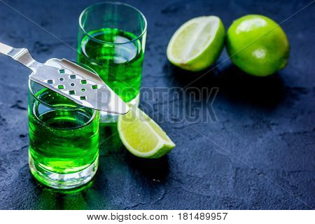 absinthe shots with fresh green lime slices on dark bar table background space for text