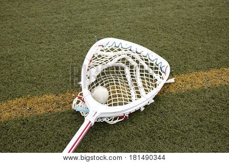 Lacrosse goalie stick with a ball in the netting on a green turf field