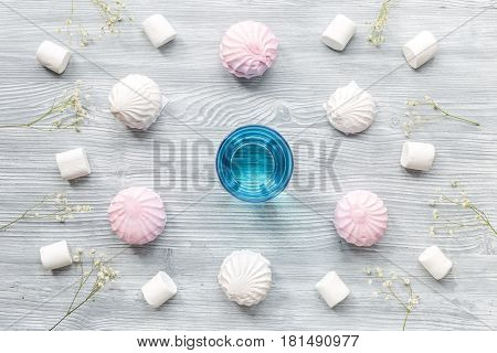 sweet marsh-mallow and cup of herbal tea for woman breakfast concept on wooden desk background top view