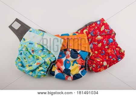 Three colorful washable cotton diapers with buttons and velcro lay on white background