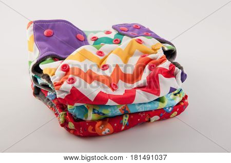 Pile of different multicolor baby cloth reusable diapers with buttons on white background