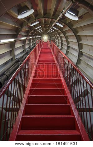 Red staircase in a round metal tunnel,