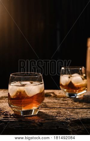 A glass of whiskey with ice on a wooden background close-up in the background of a barrel of whiskey