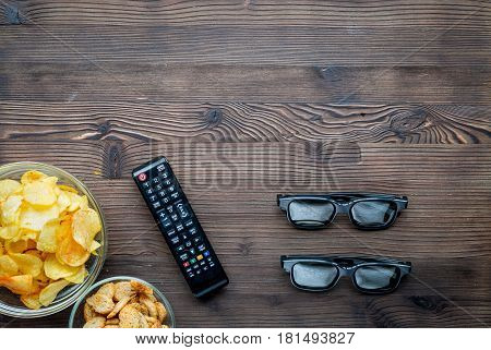 watching movies concept with chips and zapper on wooden table background top view mock up
