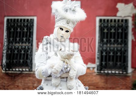 Snow white carnaval mask standing in front red wall background with iron lattice on the window holding toy bear, Venice, Italy.