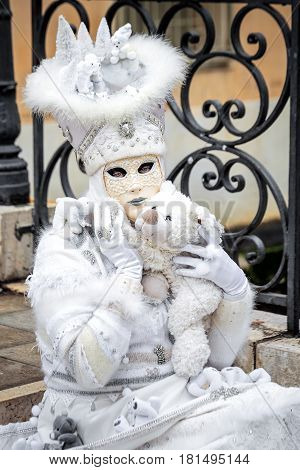 Venice white carnaval mask sitting on stairs with toy bear,Italy.