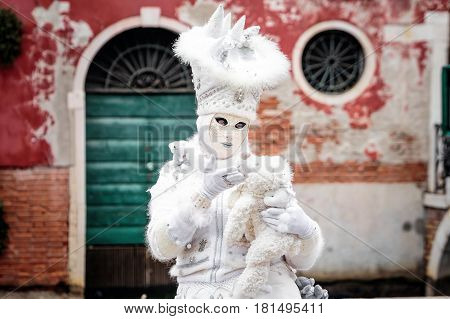Snow white carnaval mask standing in front red wall background with green iron gate and round windows holding toy bear, Venice, Italy.