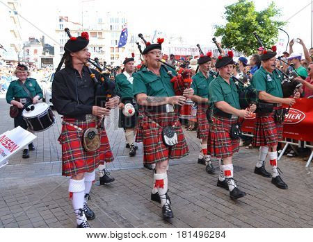 LE MANS FRANCE - JUNE 13 2014: Scottish bagpipe band is marching down the street during parade of pilots racing in Le mans France.