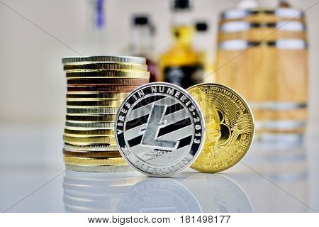 Cryptocurrency physical silver and gold coins near a barrel
