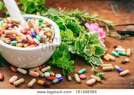 Herbs And Pills In A Mortar On Wooden Background
