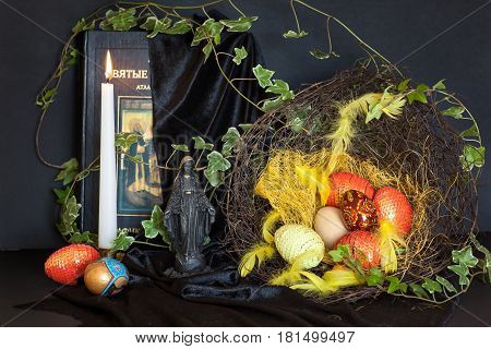 Easter still life in old style. A nostalgic decoration with hand-decorated hand-painted eggs, a burning candle, a holy book and a statue of the black Madonna