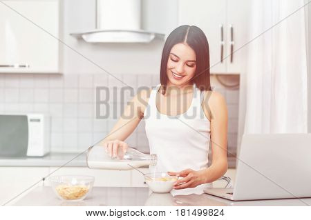 A young woman prepares a low-calorie breakfast on a prescription while looking at her laptop. Diet, apples, muesli, corn flakes - the concept of a healthy diet. Cooking food in your kitchen.
