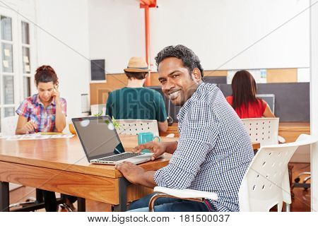 Man as startup founder in coworking office using laptop