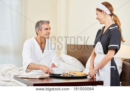 Maid bringing breakfast as room service to man in hotel room