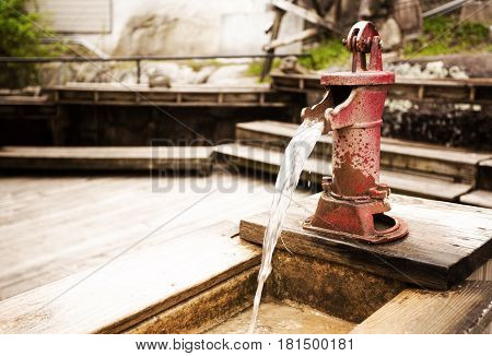 A small red vintage steel water pump mounted on a plank of wood with water pouring out of the spout